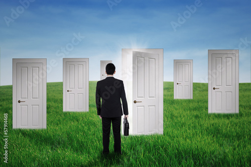 Businessman walking into opportunity doors
