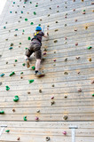 Young man climbing outdoor climbing wall