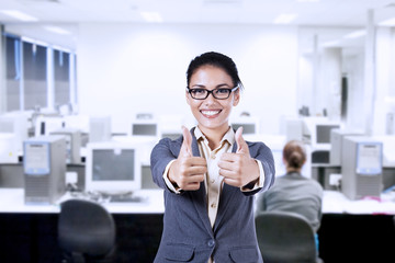 Businesswoman showing thumbs up in the office
