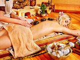 Woman getting stone therapy massage .