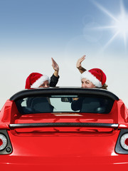 Two Santa Claus waving of the hand in a roadster