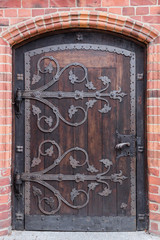 Old stylish door in Polish cathedrak in Koszalin. Gothic style.