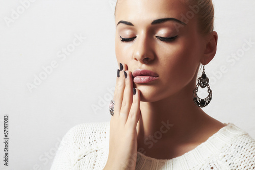 beautiful blond woman in white woolen sweater.Jewelry and Beauty