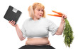 Obese woman with fresh carrot and bathroom scale.