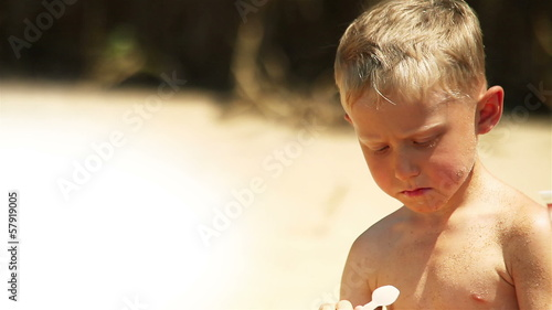 Little boy eats yogurt on the sunny beach