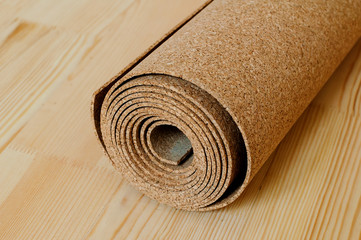 A roll of cork lies on the wooden floor