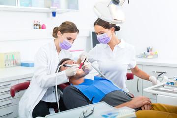 Patient bei Zahnarzt - Behandlung mit Bohren
