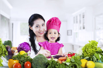 Mother and daughter cooking vegetable salad