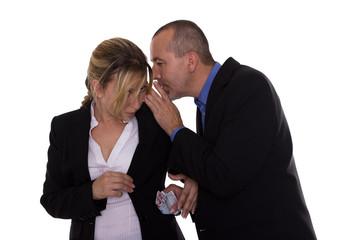 Frau tuschelt mit Mann