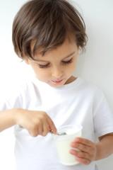 little boy eating yogurt