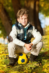 The schoolboy with football's ball in autumn park