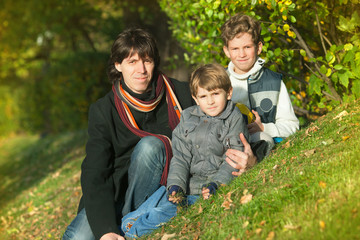 The father and two boys sit on hill slope