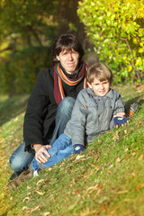 The man and boy sit on slope in autumn park