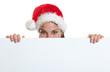 Lachende Frau mit Nikolausmütze versteckt hinter Werbetafel