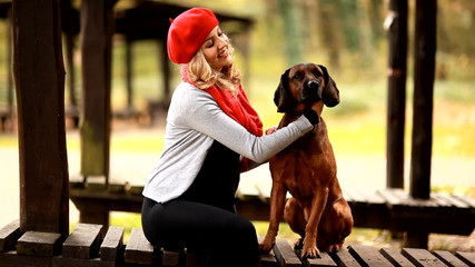 Pretty woman with dog in park