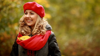 Falling leaves on pretty blond girl in park