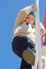 Cute active child climbing up a ladder in the park