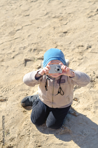 Funny little child holding a compact camera