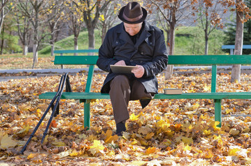 Elderly man on crutches using a tablet in the park
