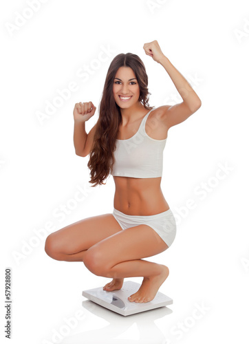 Happy woman celebrating her new weight on a scale
