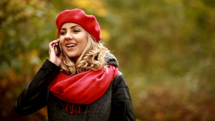 Beautiful blond woman talking on the phone in park