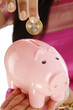 Woman hand inserting a coin into  piggy bank
