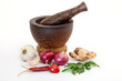 Mortar and pestle with various spices on white