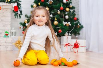 Happy little girl with mandarins