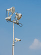Floodlight with surveillance cameras in blue sky