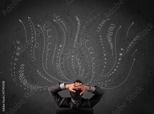 Businessman thinking with sketched arrows in front of a chalkboa