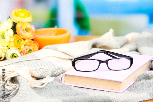 Composition with old book, eye glasses, candles, flowers and