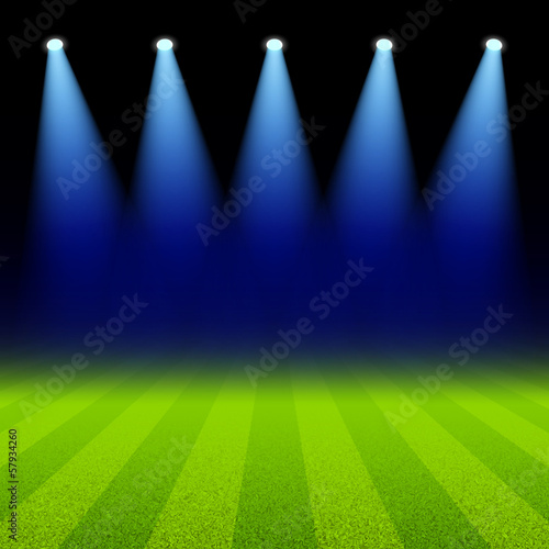 Bright spotlights illuminated green soccer field