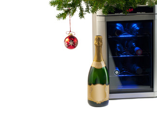 Wine refrigerator and bottle of champagne under Christmas tree.