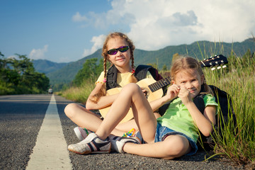 two girls with backpacks sitting on the road