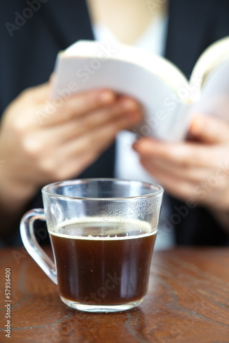 coffee in glass cup and women reading a book on background