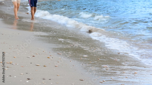 Young couple running on the beach in slow motion