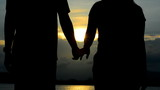Young couple holding hands silhouettes on sunset