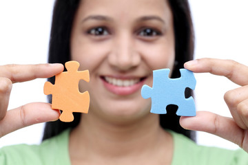 Young Indian woman holding jigsaw puzzle pieces