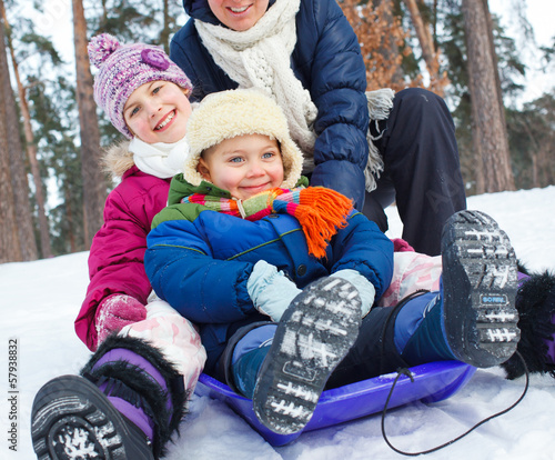 Funny family is sledging in winter-landscape