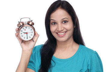 Young indian woman holding antique alarm clock against white