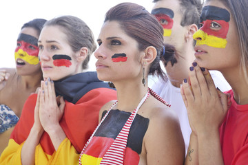 Group of german soccer fans concerned about team performance.
