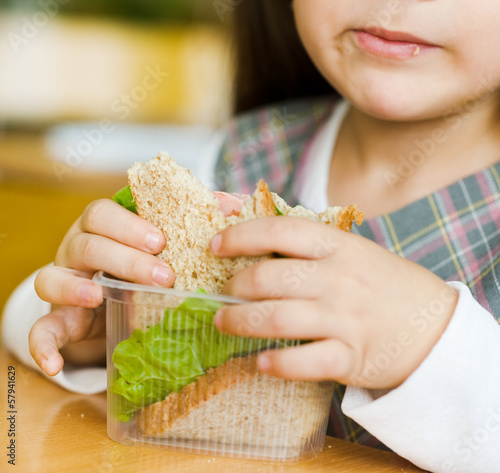 closeup schoolgirl with sandwich in classroom