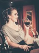 Beautiful young girl with glass of red wine in a restaurant
