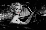 Woman with red lips in retro car against night city