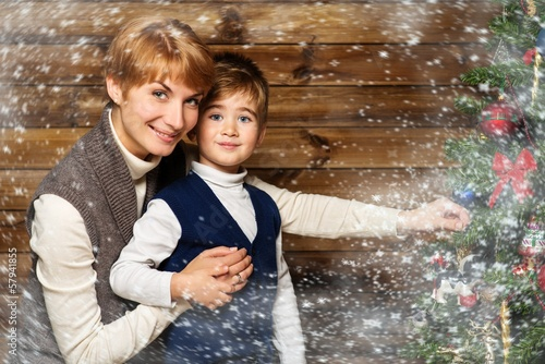Happy mother and her lIttle boy decorating christmas tree