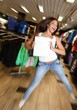 Beautiful happy brunette girl with shopping bag jumping