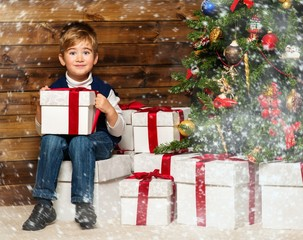 Little boy with gift box under christmas tree in wooden house in