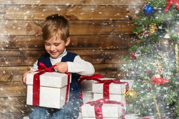 Little boy with gift box under christmas tree