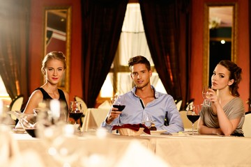 Young friends with glasses of red wine in restaurant