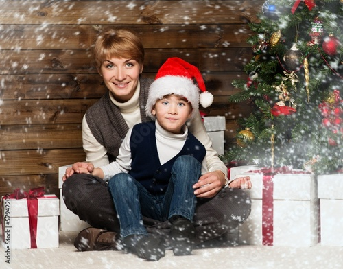 Happy mother with her child under christmas tree